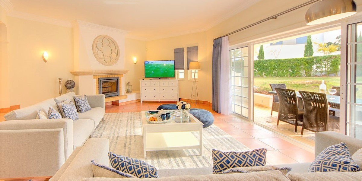 Bright Living Room With Patio Doors Out To Garden And Pool